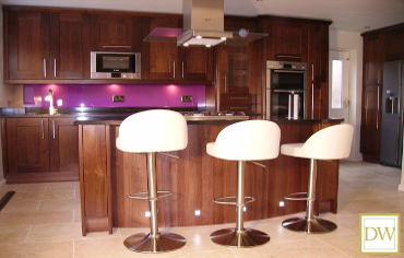 Luxury walnut kitchen with curved island and feature glass splash-back.