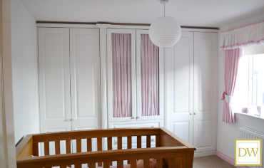 Custom made fitted wardrobes featuring central glass doors and moulded pilasters and cornice.