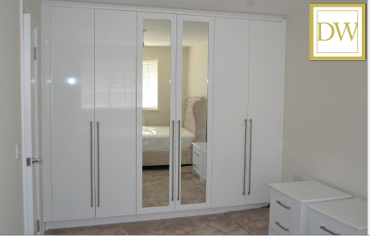 Hi-gloss custom made fitted wardrobes featurning central mirrored doors & bedside chest of drawers in ever popular white.