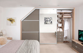 Angled door sliding wardrobes with central mirrored door and bespoke interior drawers and shelving;  together with matching bedside chest and TV /storage units.