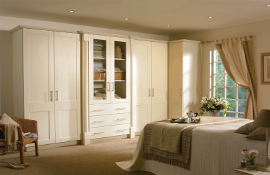 A simple yet elegant shaker design bedroom  in ivory with reeded pilasters and centre glass doors to add interest