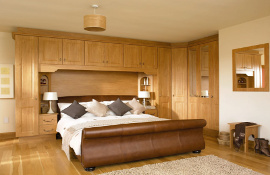 Melbourne Pippy Oak fitted bedroom furniture incorporating bedside chests, feature shelving and half mirrored doors.