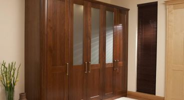 The warmth and richness of  wood -  walnut doors with 1/4 radius rounded corners and frosted insets result in a visually attractive yet practical run of units.