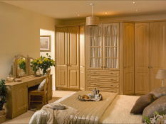 Windsor Montana oak fitted wardrobes with feature extended glass central  doors and drawers beneath and matching dressing table.