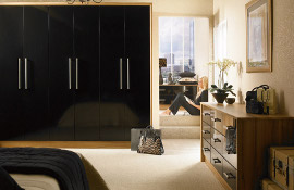 For attractive and sophisticated City living, this bedroom has a real ' New York' feel to it. The  simple styling however would look equally well in less far off  places ..like Wigan!  The wood grain side panels add warmth  and contrast to the black gloss doors.