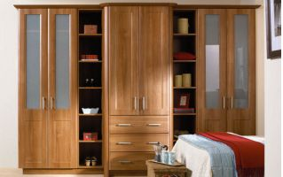 These wardrobes in warm medium walnut, feature rounded corners, frosted glass inserts and open display shelving - all resulting in a practical and eye-catching design.