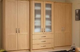 Light pear fitted bedroom furniture with central frosted glass doors and drawers beneath.