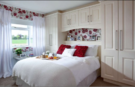 White classic shaker style fitted bedroom with over-head storage cupboards and headboard shelf.